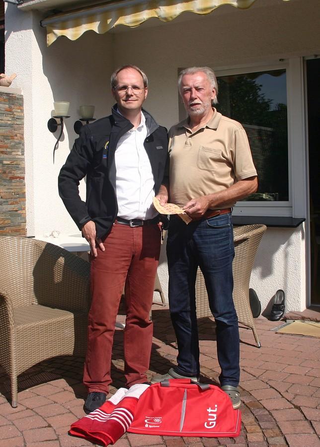 Thomas Weber von der Hüstener Kirmesgesellschaft übergibt den Hauptgewinn an Wolfgang Möller, Opa des Gewinners.