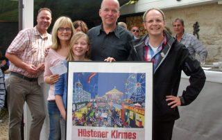 Thomas Weber, Glücksbote der Hüstener Kirmesgesellschaft (rechts) überrascht Martin Friedrich mit dem Hauptgewinn des Ballon-Weitflug-Wettbewerbs. Mit ihm freuen sich Familie und Freunde.